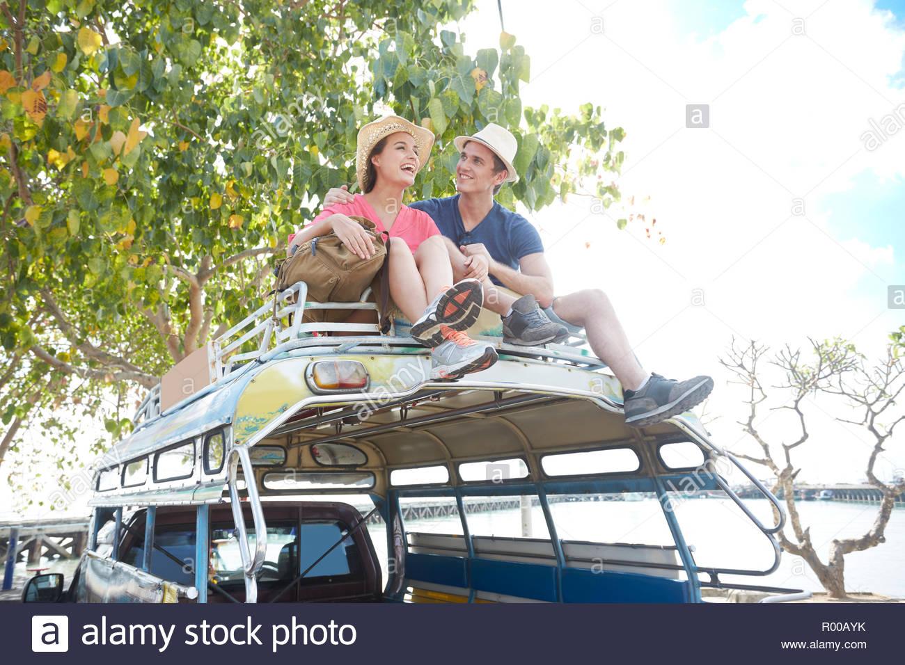 Jeune couple assis sur le toit des autobus d'excursion Photo Stock
