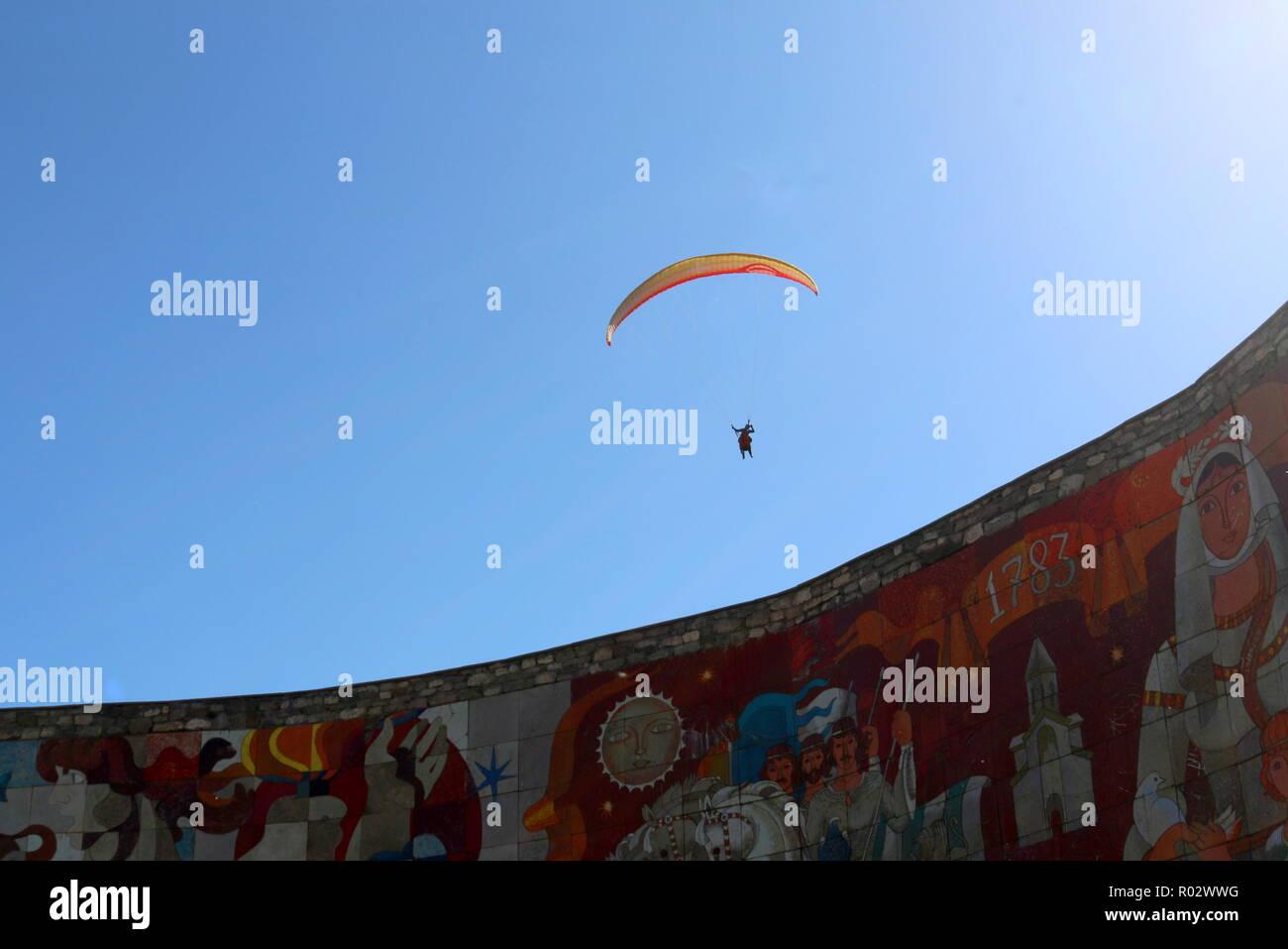 Un hangglider avec une ouverture du parachute sur le Traité de Georgievsk monument qui symbolise l'amitié russo-géorgien Photo Stock