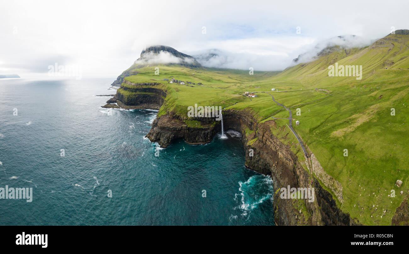 Vue panoramique aérienne de cascade et falaises, Gasadalur, Vagar et Île, Îles Féroé, Danemark Photo Stock