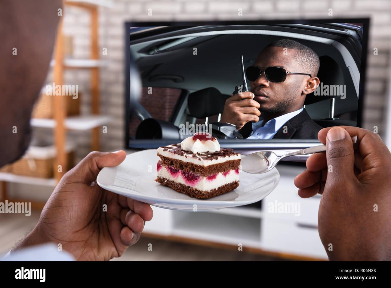 Close-up of a Man Eating feuilletée en regardant thriller film à la télévision Photo Stock