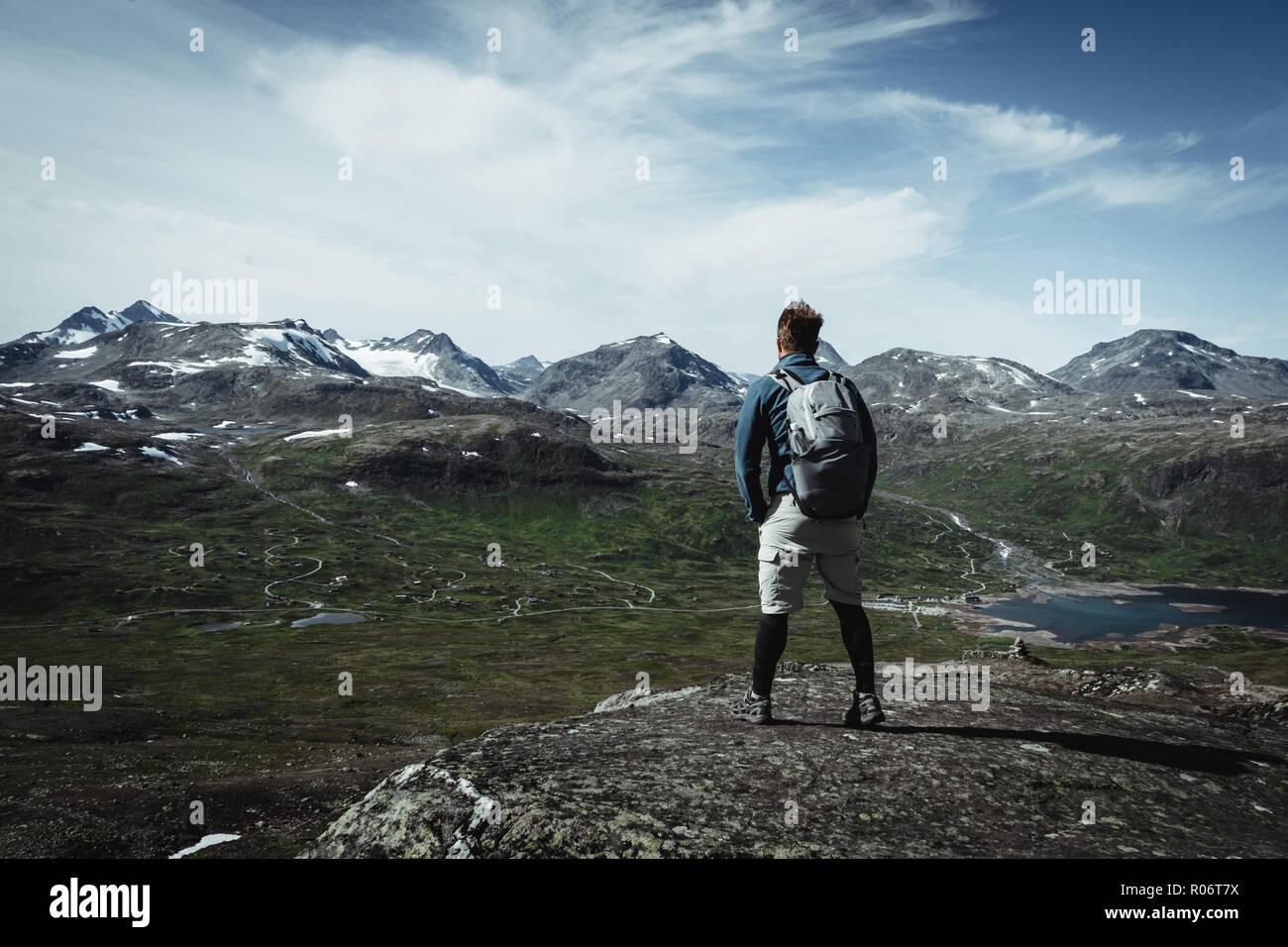 Randonneur l'homme avec un sac à dos sur le pic haut. Concept d'un sentiment d'accomplissement. Randonnée dans le parc national de Jotunheimen Oppland, Norvège Photo Stock