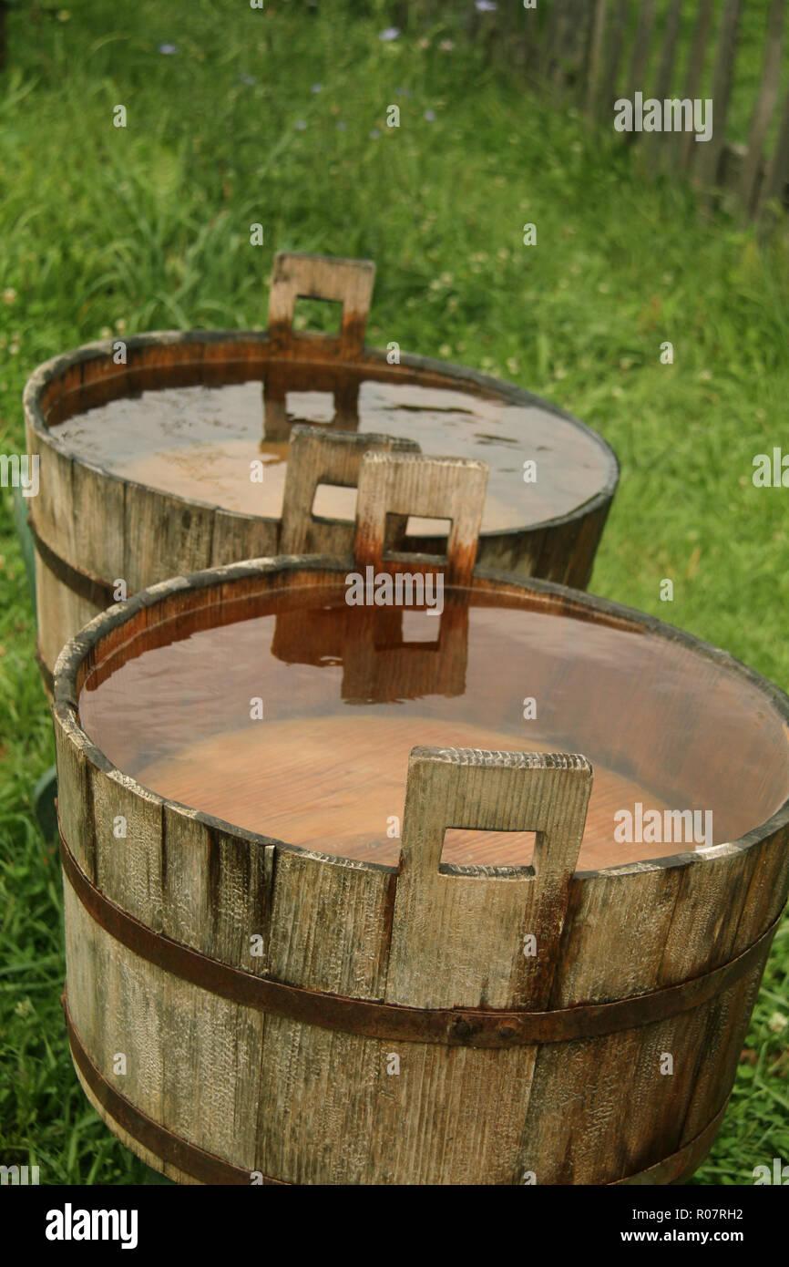 Des tonneaux de bois rempli à ras bord avec l'eau de pluie Photo Stock