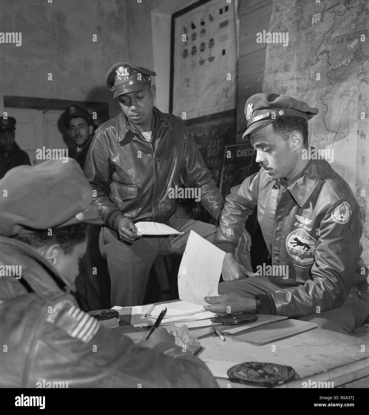 Exposé à Tuskegee Airmen à Air Base, Woodrow W. Crockett, debout au centre, Edward C. Gleed, Lawrence, KS, classe 42-K, officier des opérations du Groupe, assis sur la droite, et l'Aviateur non identifiés assis sur la gauche, Ramitelli, Italie, Toni Frissell, Mars 1945 Photo Stock
