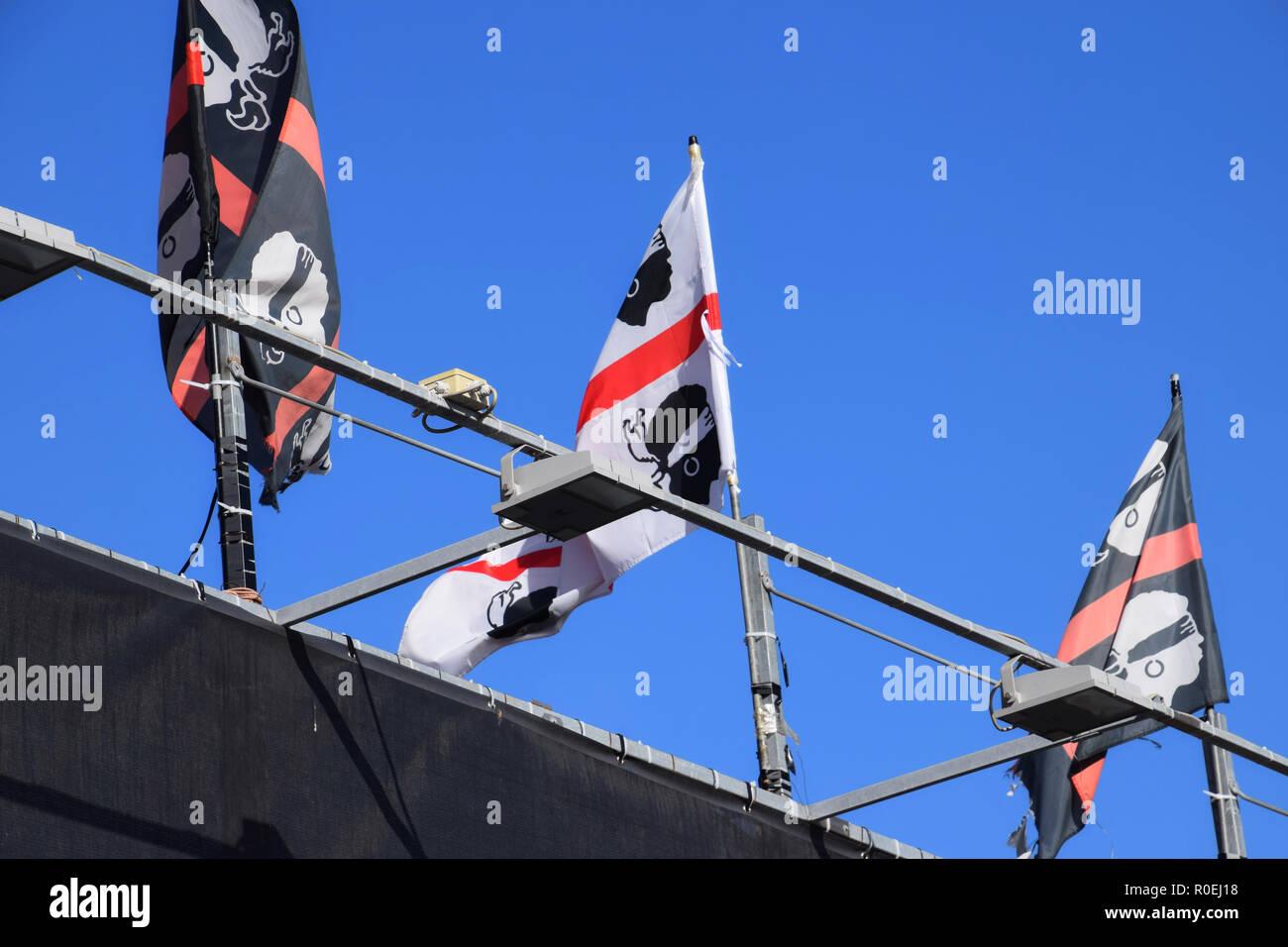 CASTELSARDO, ITALIE - Le 12 septembre 2018: sarde trois drapeaux flottant au vent, beaucoup de drapeaux de nationalisme sarde en face de bleu profond et c Photo Stock