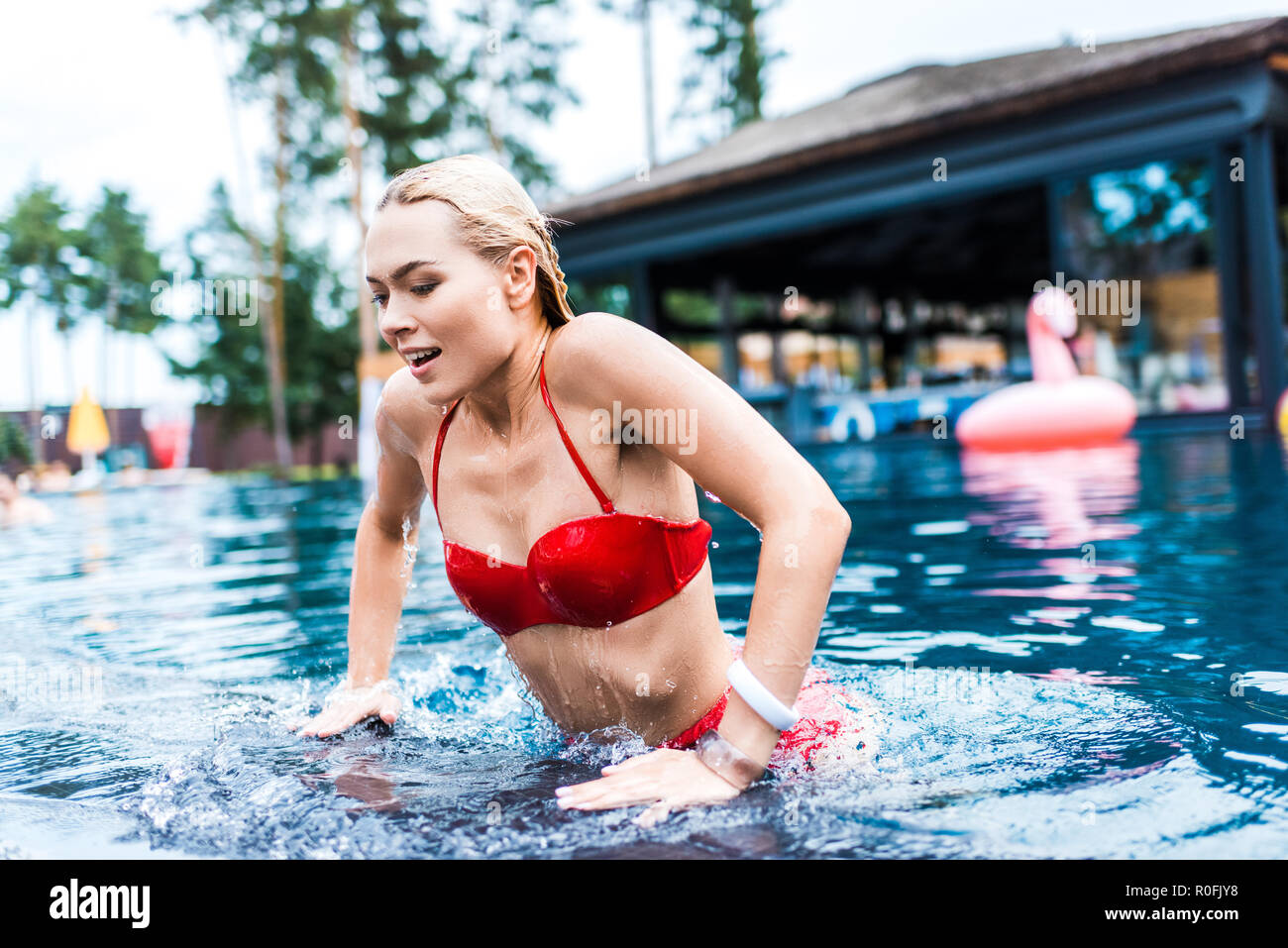 Young attractive smiling woman swimming in pool Photo Stock