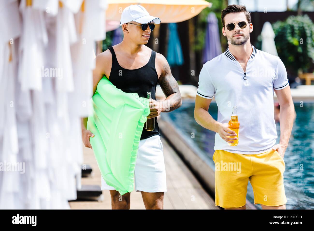 Homme amis marchant avec matelas gonflable et la bière proche piscine Photo Stock