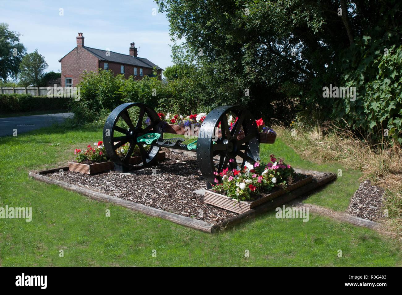 Fleurs en bordure de bégonias et géraniums avec un outillage agricole comme un élément central.Stalmine village BlackpooL Lancashire England UK Photo Stock