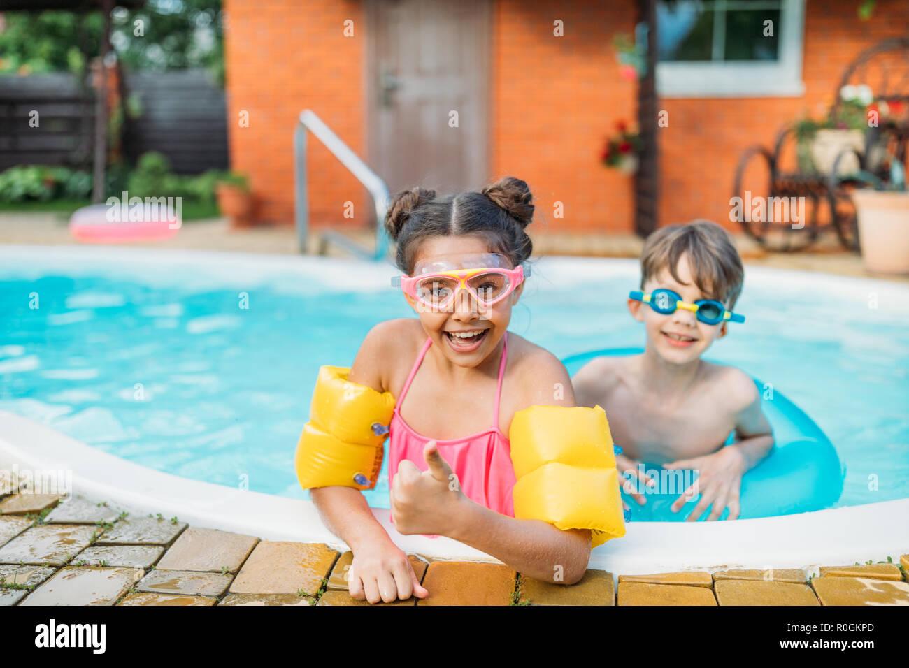 Peu de frères et sœurs en natation piscine ensemble sur journée d'été Photo Stock