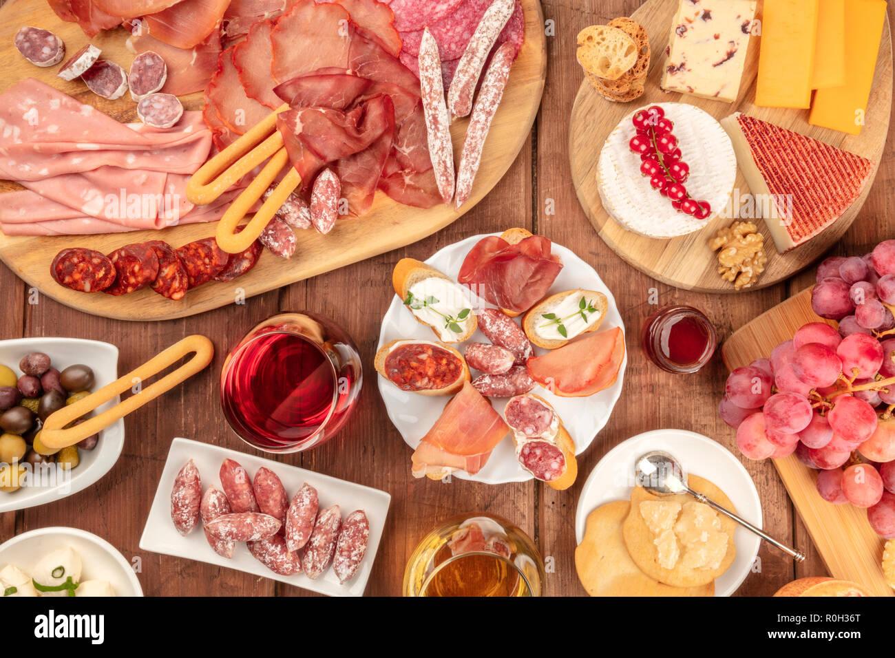 Dégustation de charcuterie. Une photo d'un grand nombre de saucisses et de jambons, charcuteries, et une assiette de fromage, tourné à partir de ci-dessus, sur un fond rustique avec du vin rouge Banque D'Images