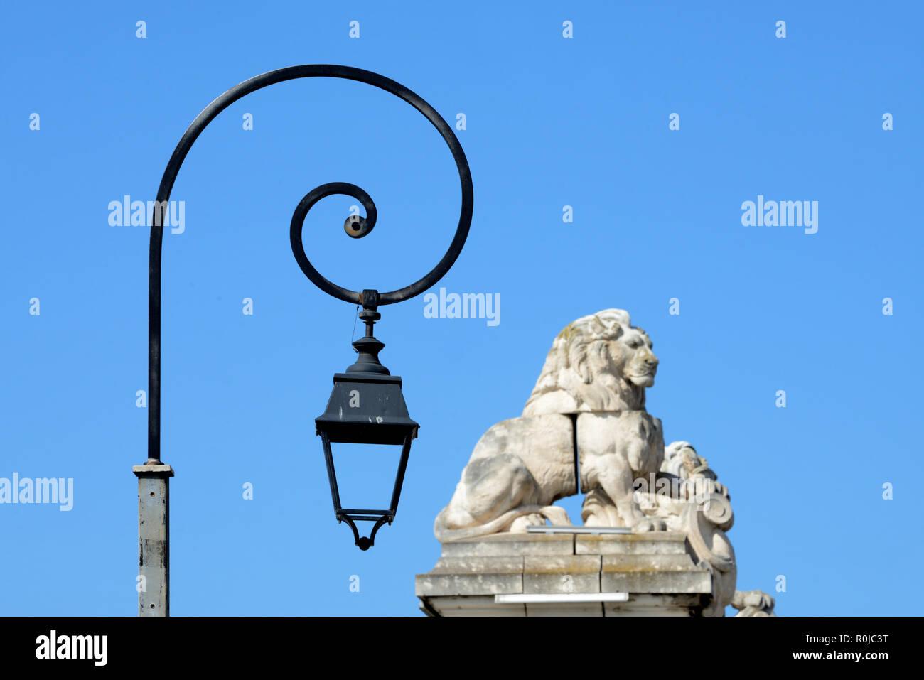 Lumières de rue contemporain ou lampes sculptées en pierre et les Lions au sommet de colonnes ou de l'ancien pont suspendu sur le fleuve Rhône à Arles Provence France Photo Stock