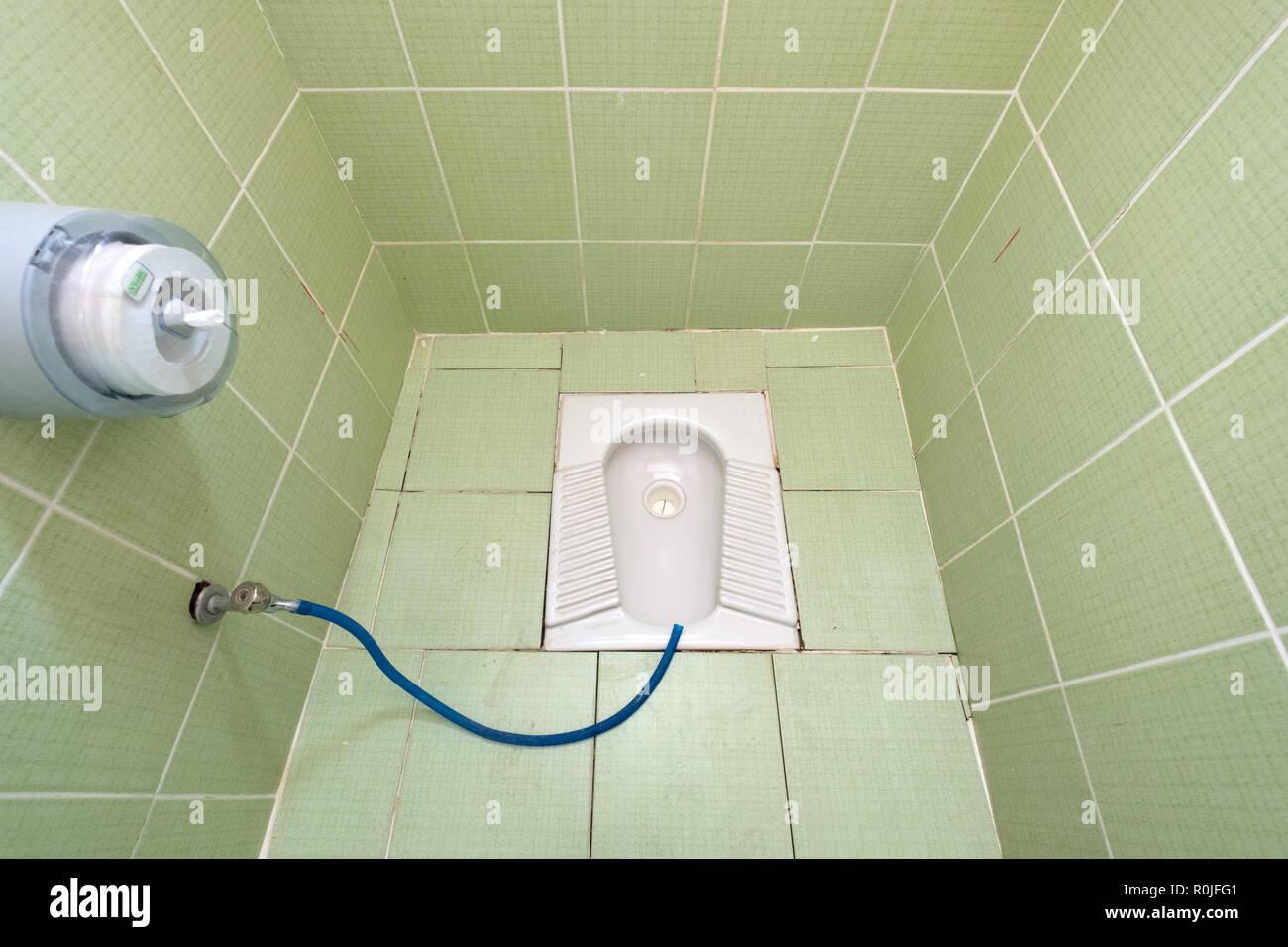 Trou dans le sol à l'accroupissement toilettes une toilette publique Photo Stock