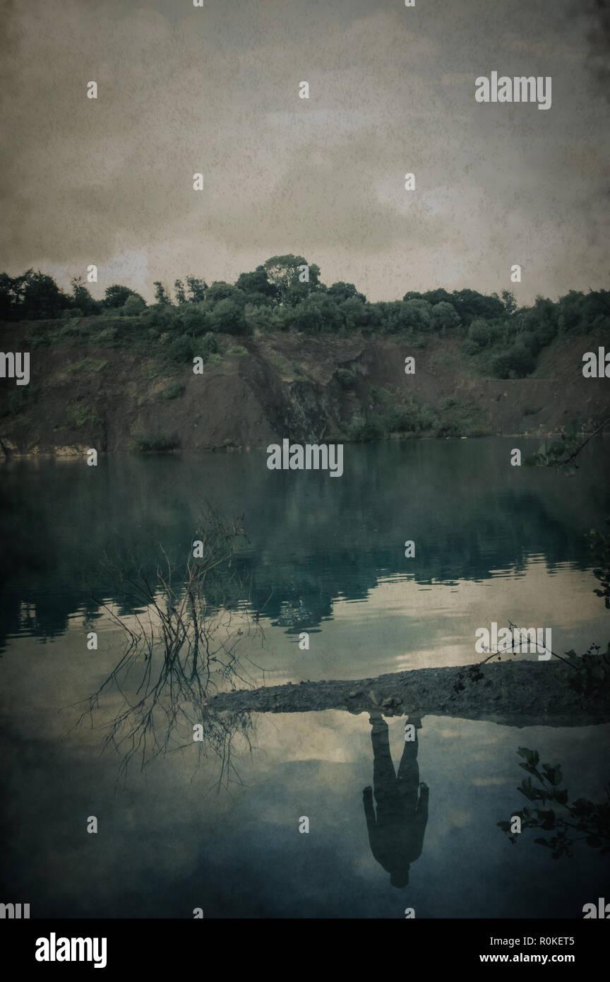 Une silhouette fantomatique de l'homme reflétée dans un lac sans que personne ne soit là. Avec un vintage, coupé modifier Photo Stock