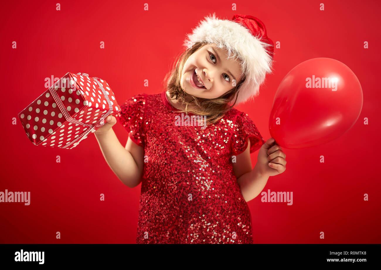 Adorable petite fille dans une robe de Noël dans un Santa s hat holding a  présent sur un fond rouge 2c3adc1e541