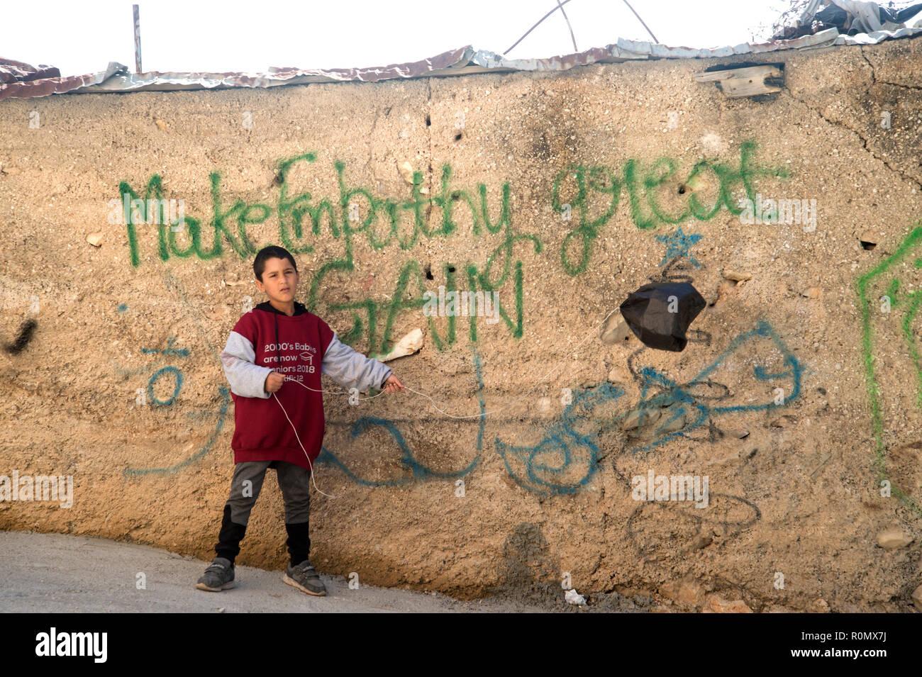 Bethléem. La Palestine. Un jeune garçon joue avec un cerf-volant fabriqué à partir d'un sac en plastique noir, en face de l'écriture en disant 'faire de l'empathie de nouveau grand'. Photo Stock