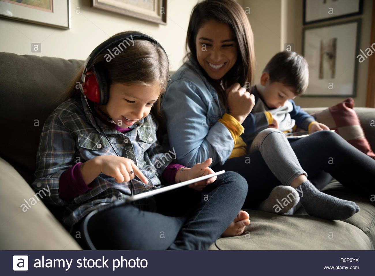 Latinx mère regardant les enfants à l'aide de tablettes numériques sur canapé Photo Stock