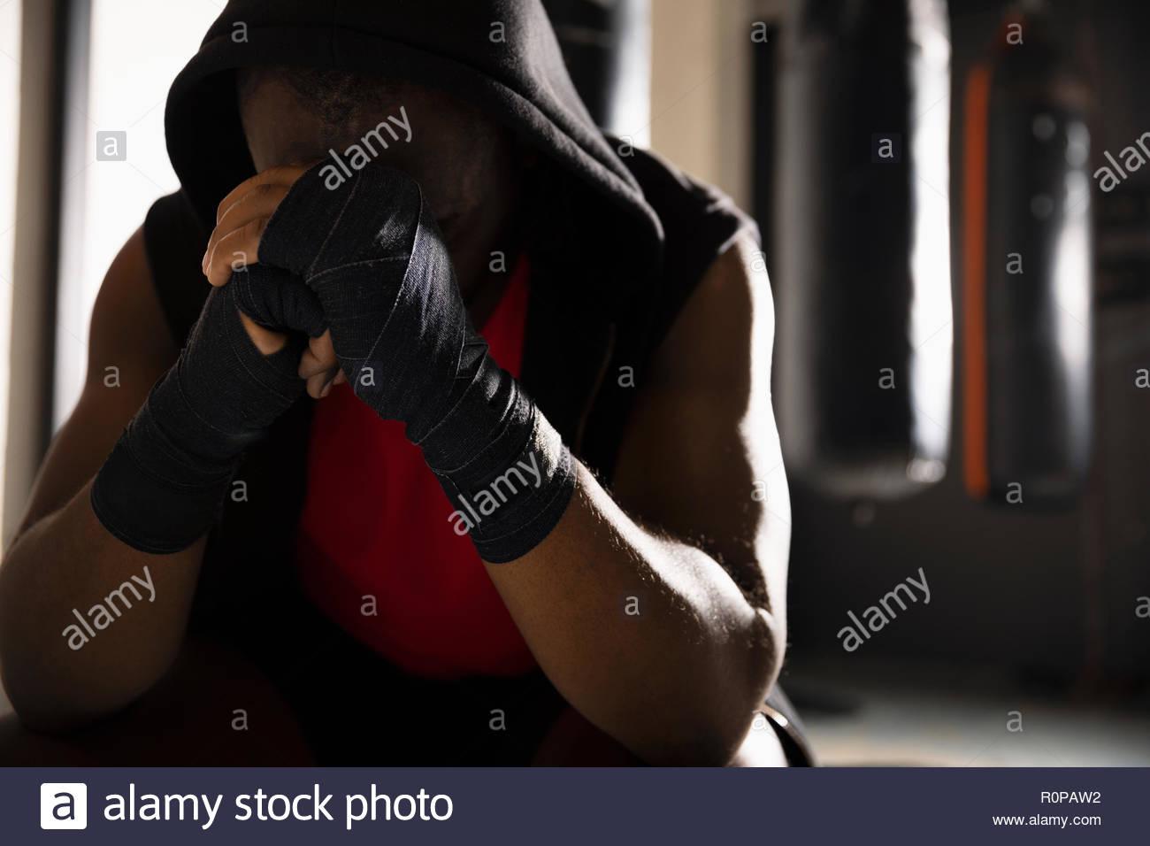Fatigué male boxer avec la tête dans les mains, se reposant dans une salle de sport Photo Stock