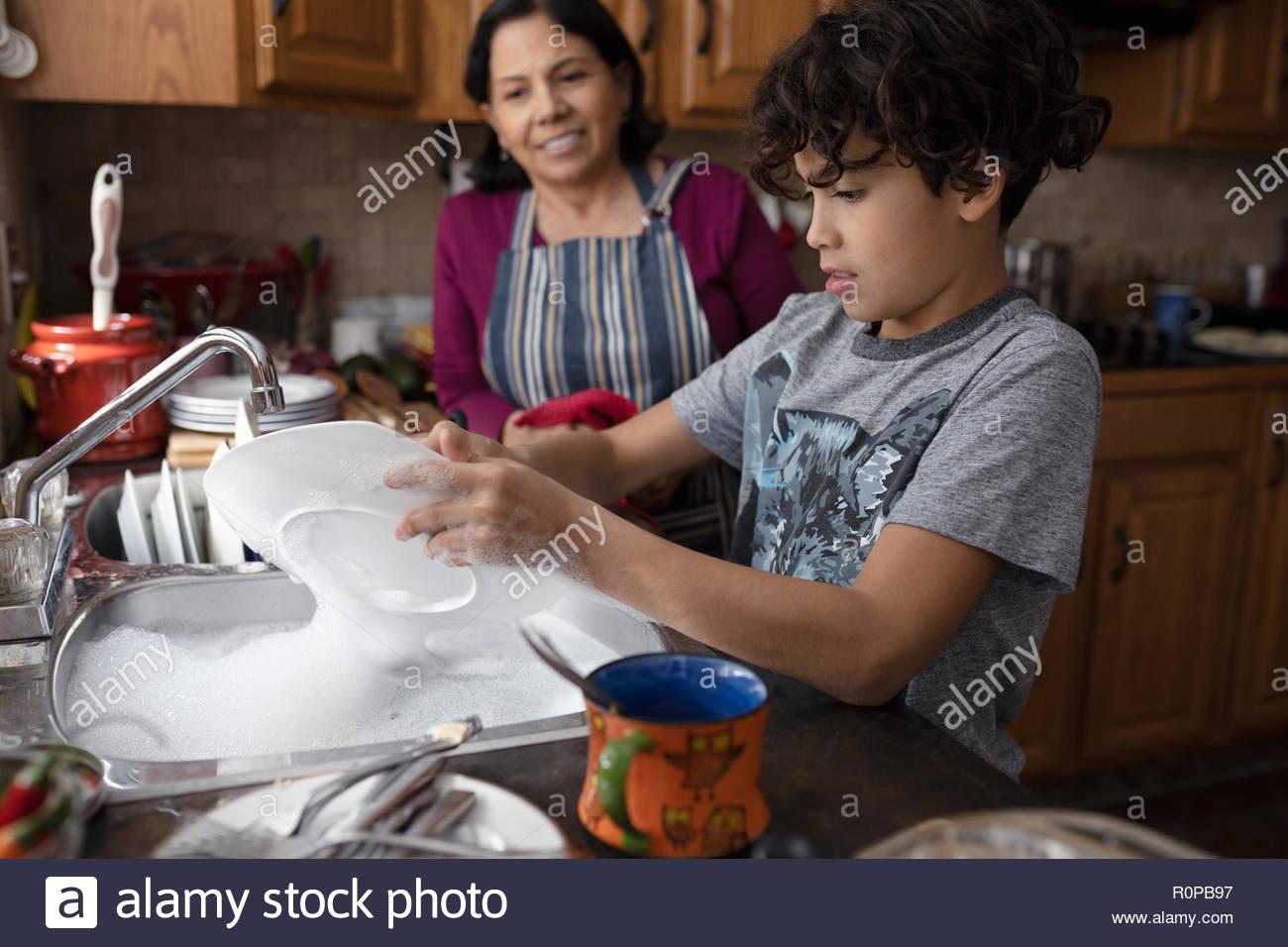 Latinx grand-mère et son petit-fils à faire la vaisselle dans la cuisine Photo Stock