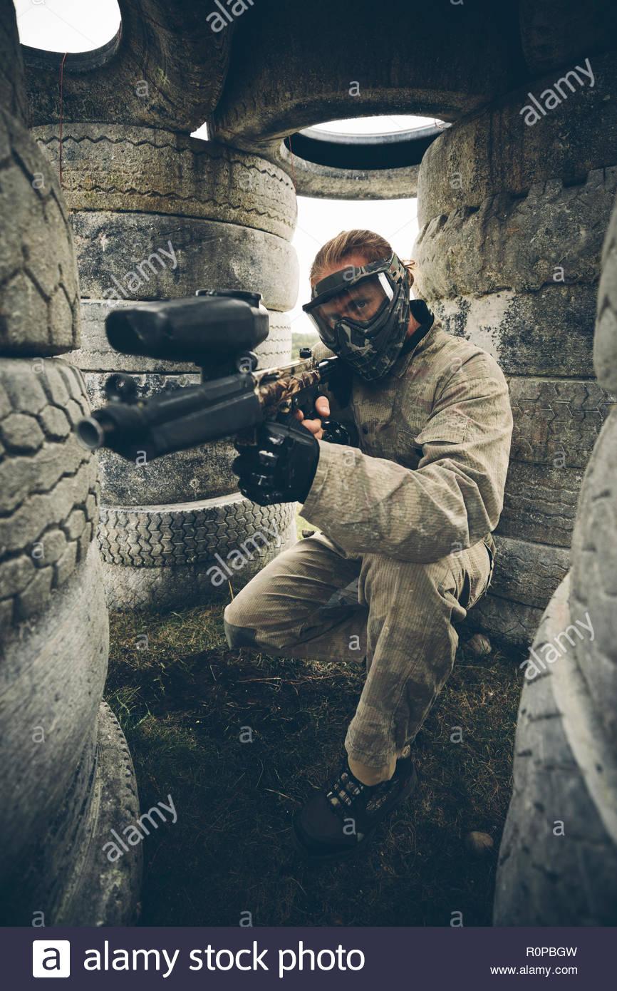 Portrait man se cachant parmi les pneumatiques, paintball Photo Stock