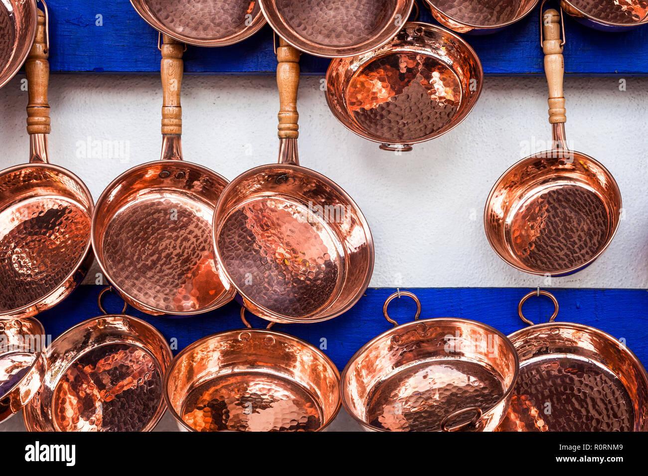 Les casseroles de cuivre accrocher sur le mur dans un marché de rue à Santa Clara del Cobre, Michoacan, Mexique. Photo Stock