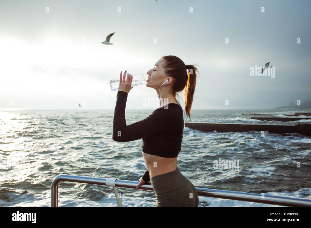 Belle femme athlète remise en forme de l'eau potable au repos après le travail à l'exercice sur la plage Banque D'Images