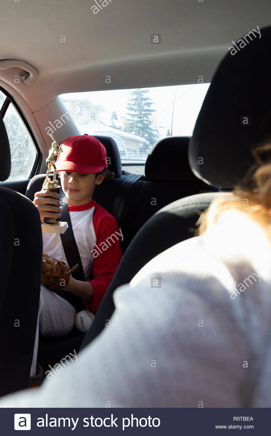 Boy in baseball uniform holding trophy in back seat of car Photo Stock