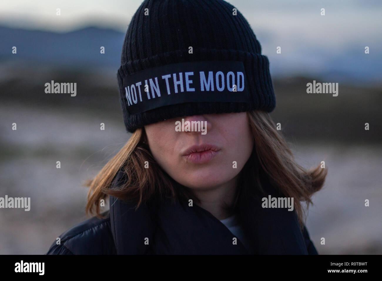 Girl wearing a black cap couvrant ses yeux avec le dit pas dans l'humeur Photo Stock
