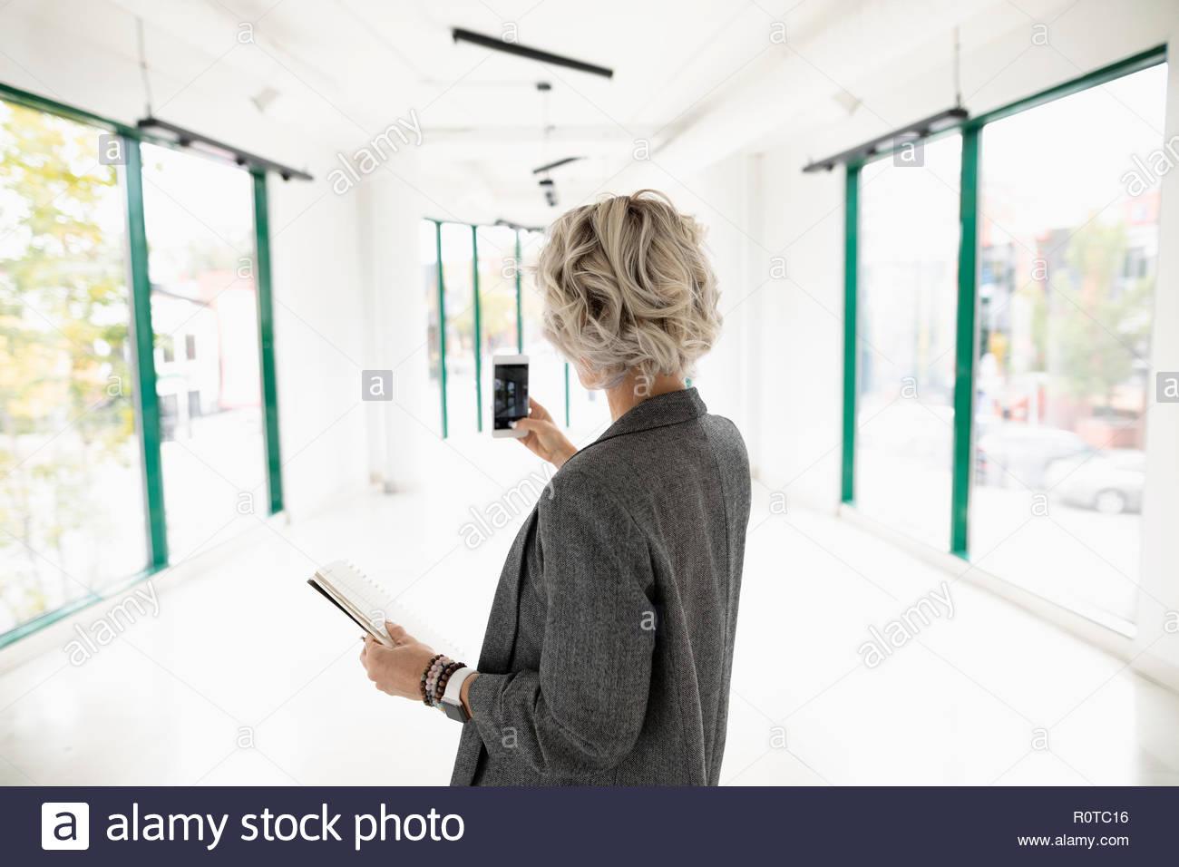 Businesswoman using camera phone, de photographier, de nouveaux espaces de bureaux vides Photo Stock