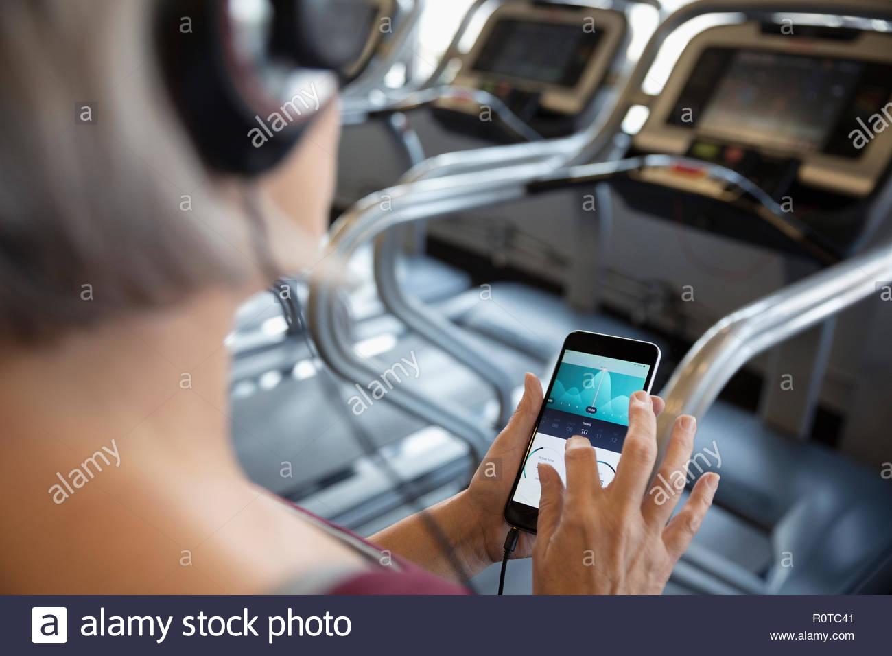 Woman on smart phone tracker remise en forme à tapis roulant dans une salle de sport Photo Stock