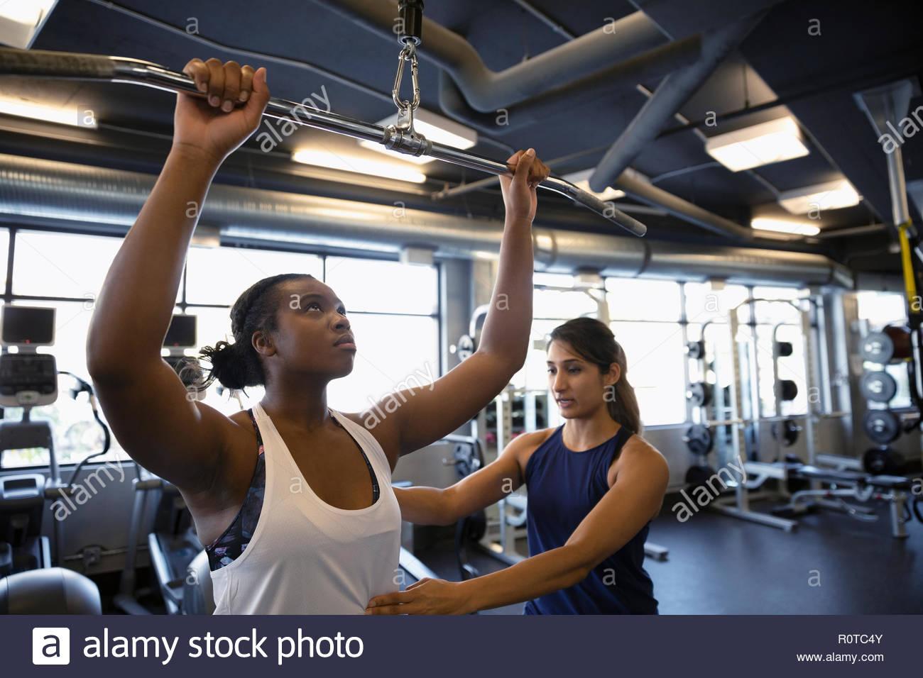 Personal trainer helping woman en utilisant l'équipement d'exercice dans la salle de sport Photo Stock