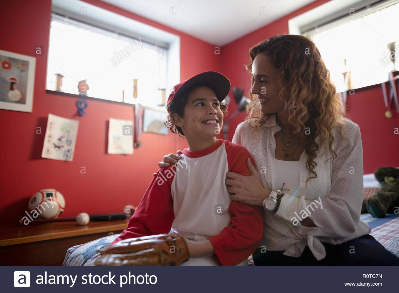 Latinx mère parler aux fils en uniforme de baseball Photo Stock
