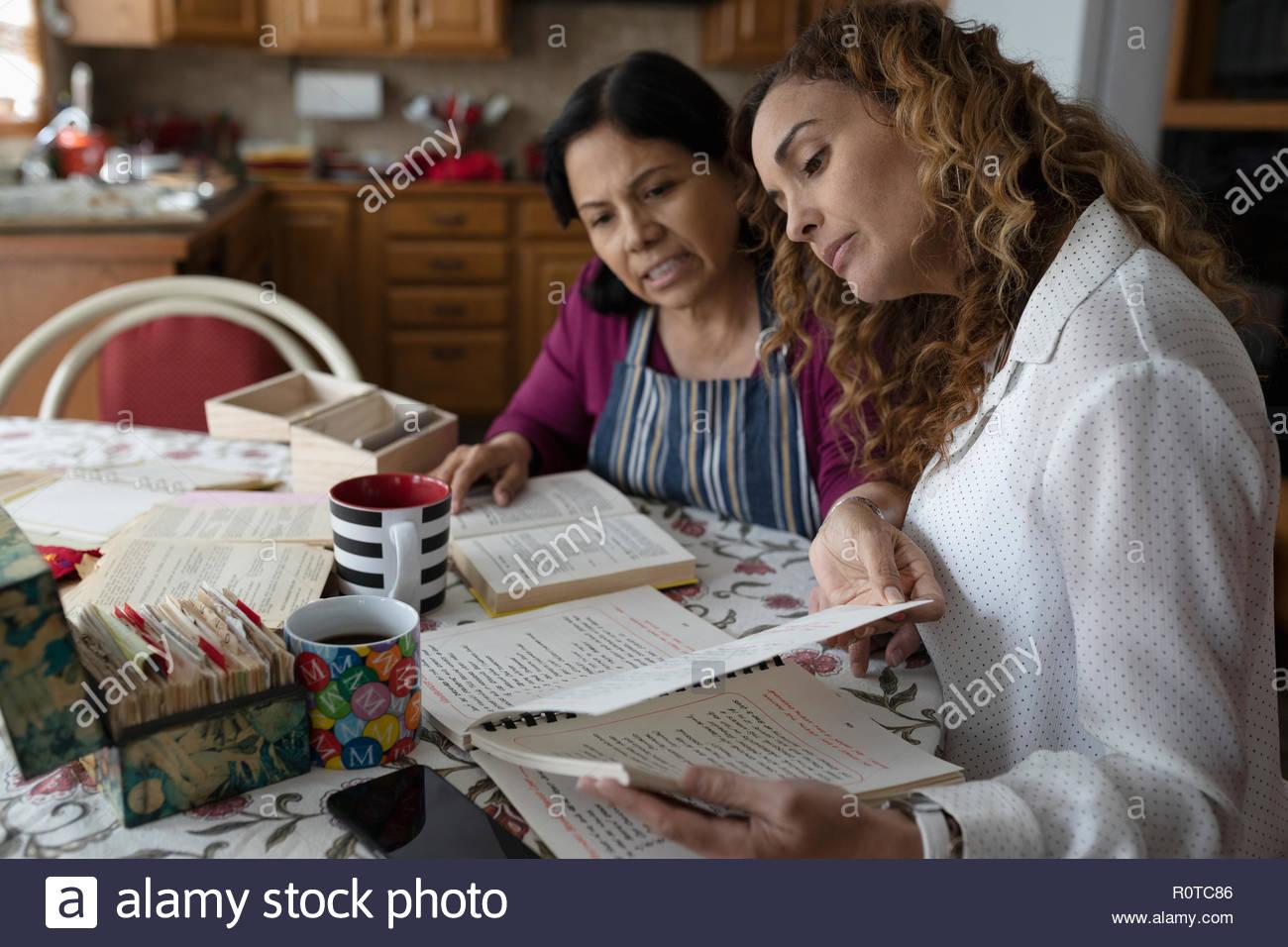 Fille Latinx et senior à la mère au livre de recettes dans Cuisine Photo Stock