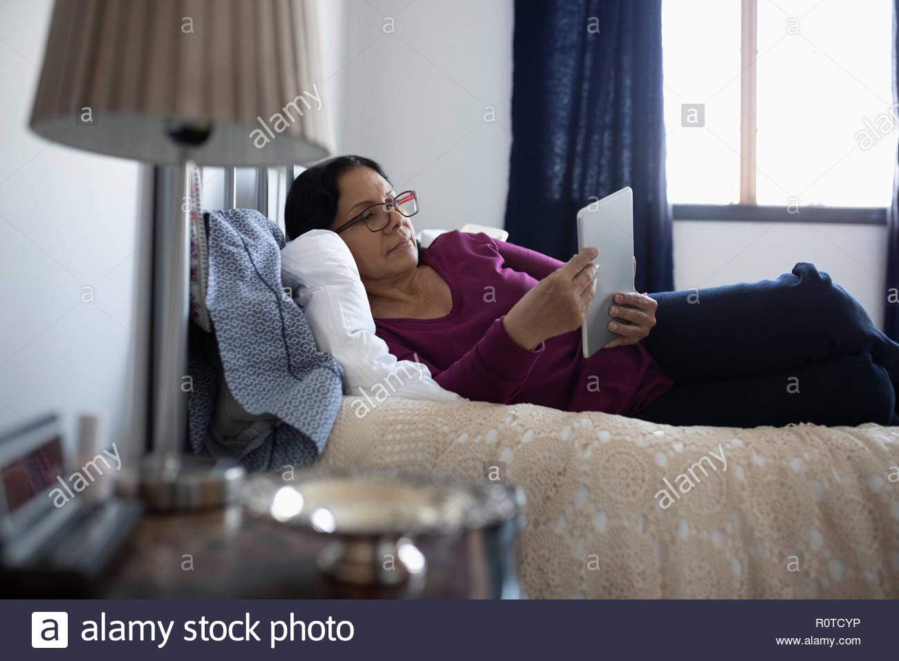Latinx senior woman relaxing, Sitting on bed Photo Stock
