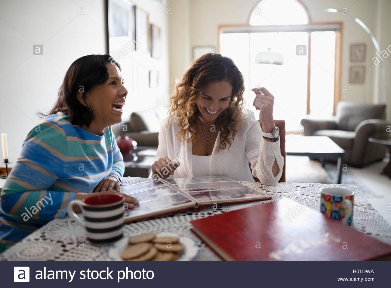 Fille Latinx heureux et la haute mère regardant l'album photo Photo Stock