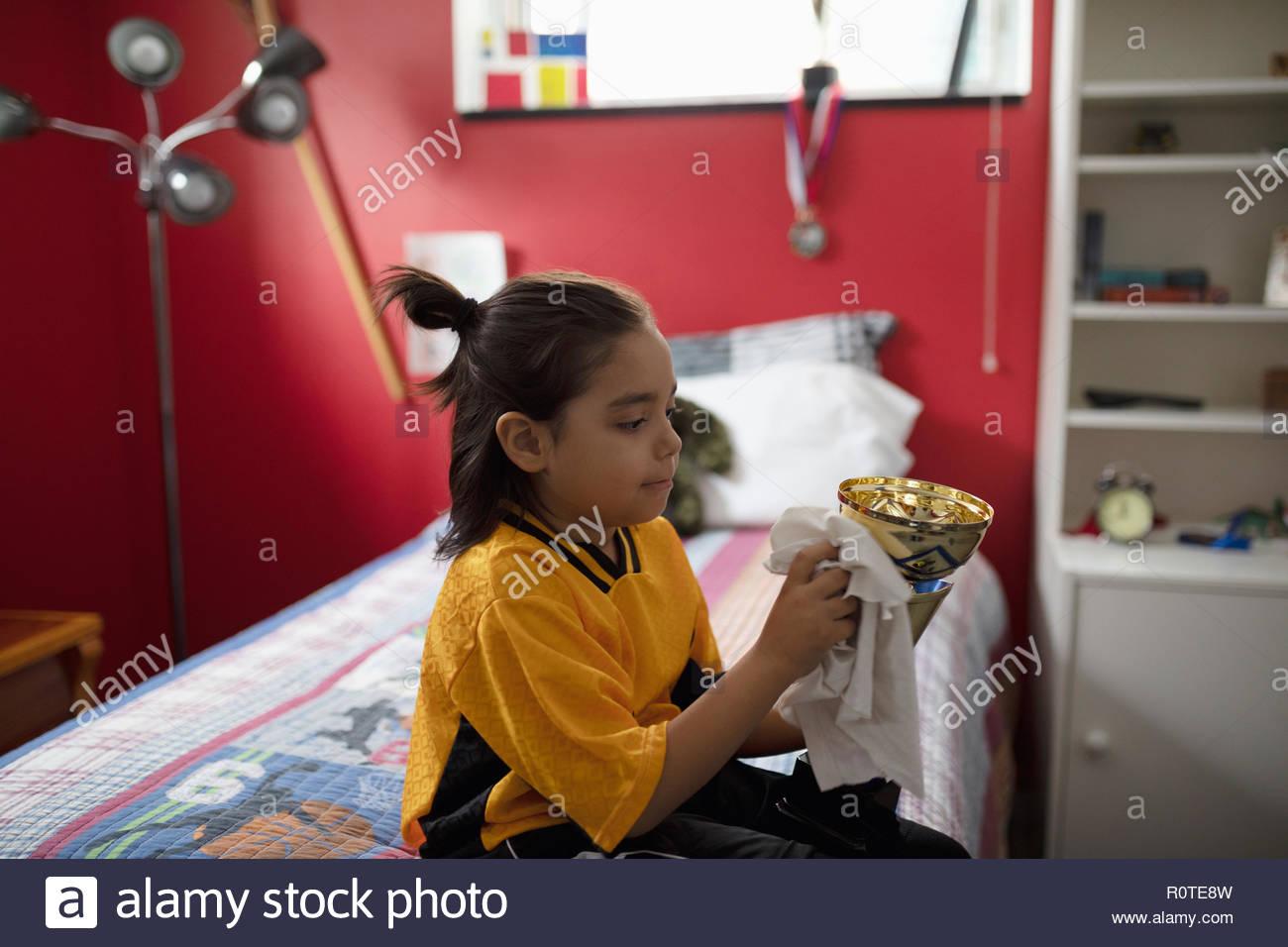 Garçon en uniforme de football trophée polissage on bed Photo Stock
