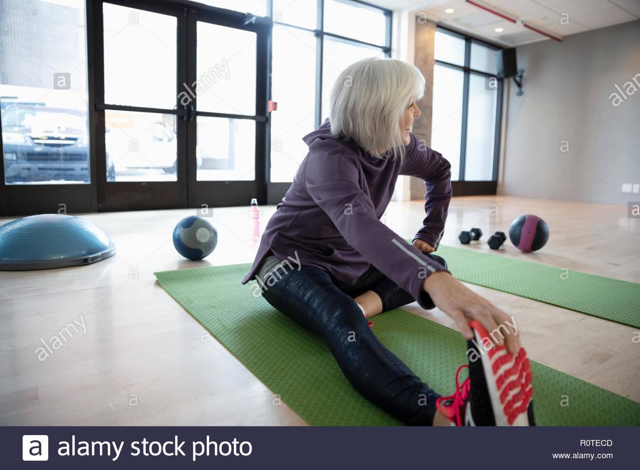 Senior woman stretching leg in studio Photo Stock