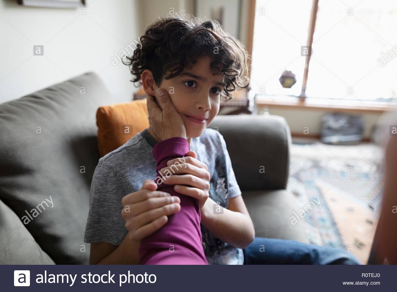 Grand-mère affectueuse de toucher de visage Latinx petit-fils sur canapé Photo Stock