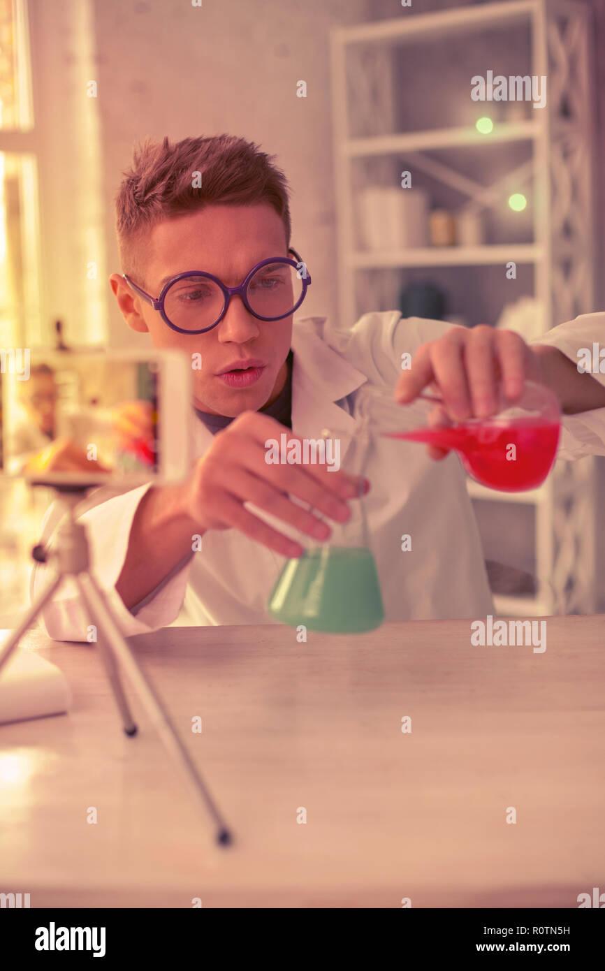 Jeune homme curieux à la recherche sur les tubes à essai Photo Stock