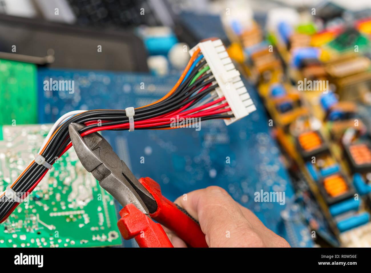 Élimination des déchets électroniques par une pince dans la main du travailleur. Connecteur, câble d'alimentation, carte mère d'ordinateur. Circuits imprimés colorés pile. PC démonté les pièces. Photo Stock