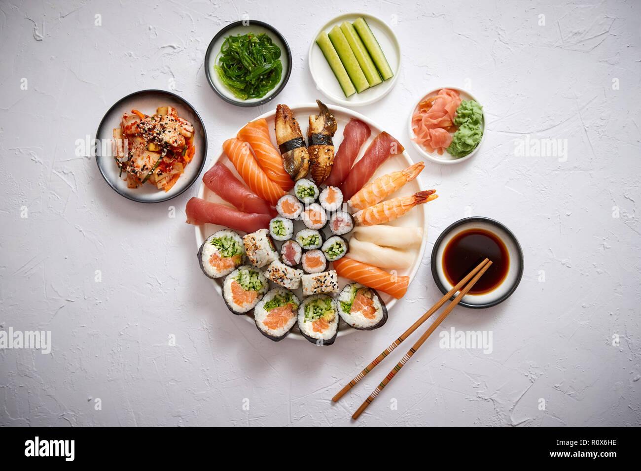 Différents rouleaux de sushi placé sur la plaque ronde en céramique Banque D'Images