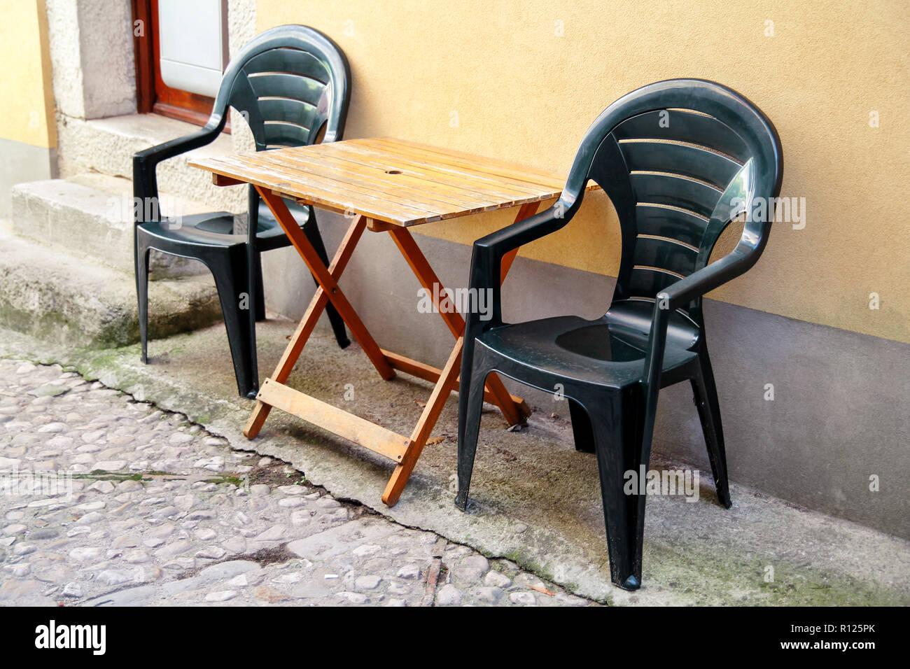 Des chaises en plastique vert et table en bois en face de la