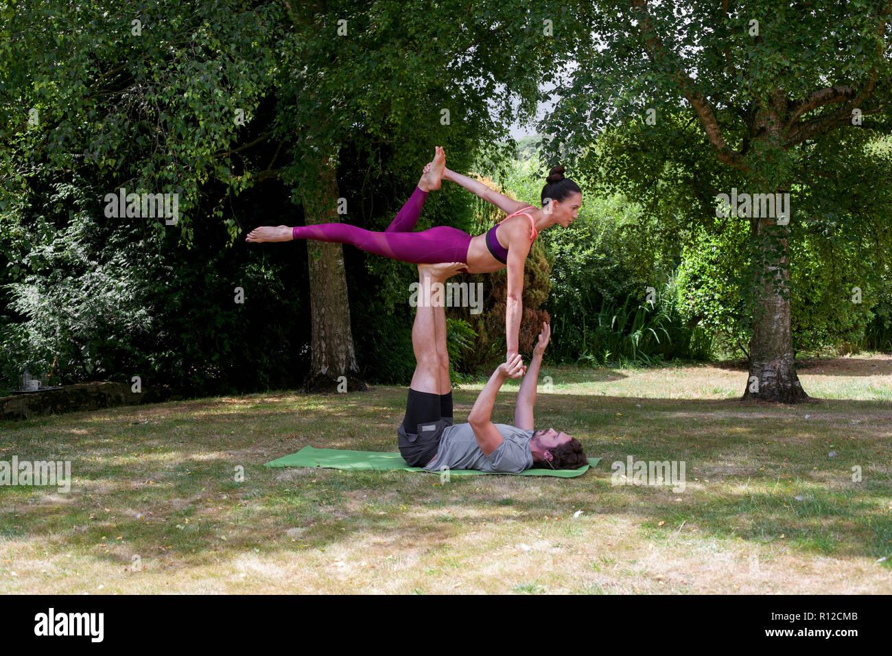 Young man practicing yoga in jardin, allongé sur le dos sur pieds femme d'équilibrage Banque D'Images