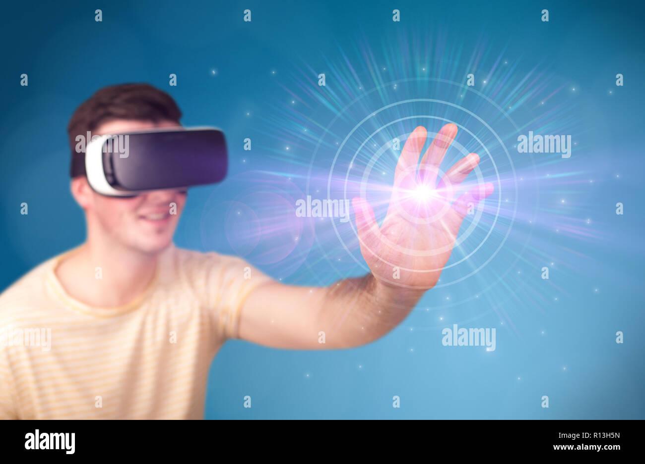 Les jeunes impressionné homme portant des lunettes de réalité virtuelle avec cercles bleus autour de son doigt Photo Stock