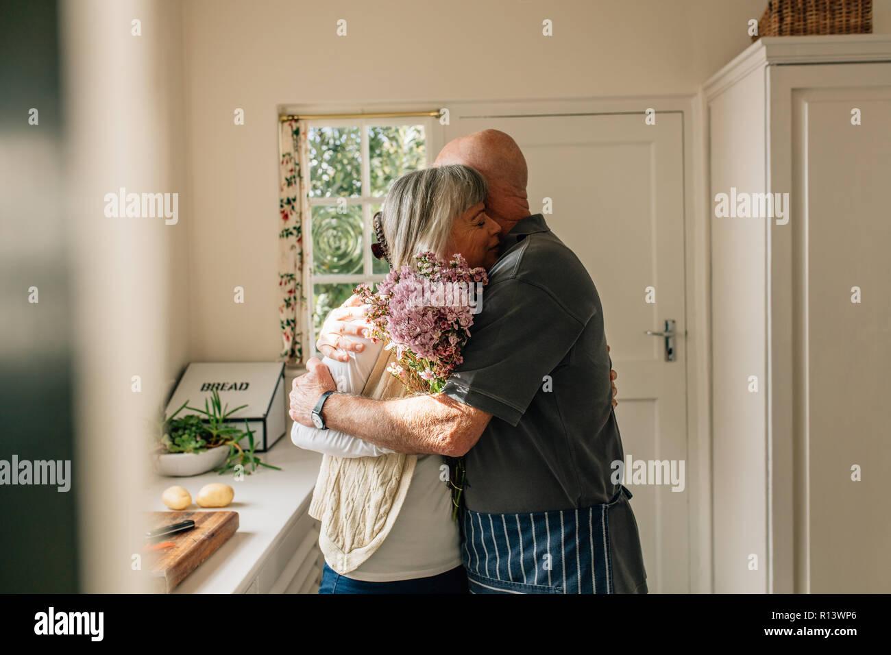 Man Hugging Sa Femme Debout Dans La Cuisine Man Exprimant