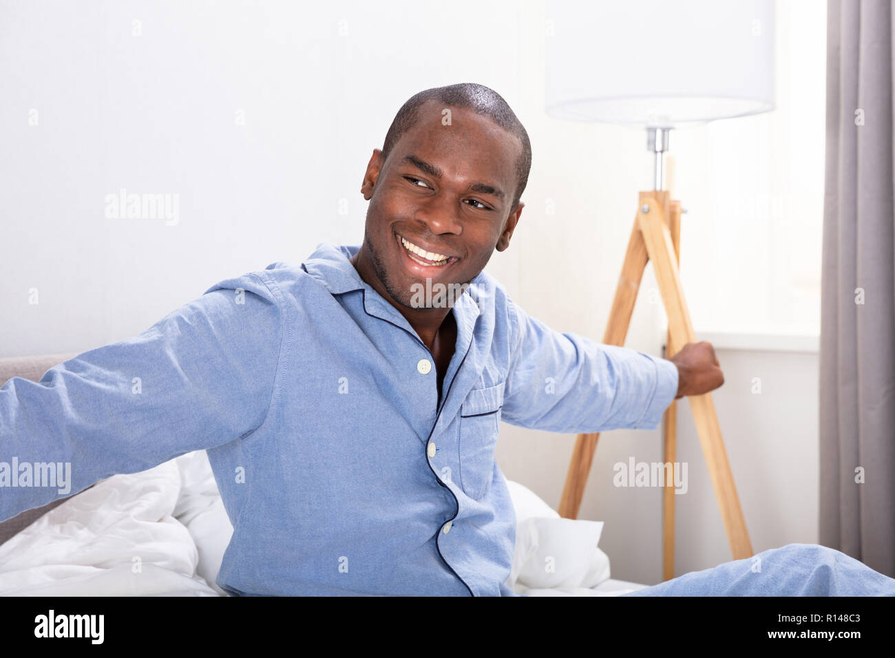 Portrait Of A Happy Young African Man Sitting on Bed Banque D'Images