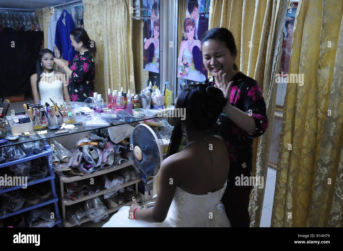 Epouse cambodgienne, w/ hairstylist, se préparer pour un