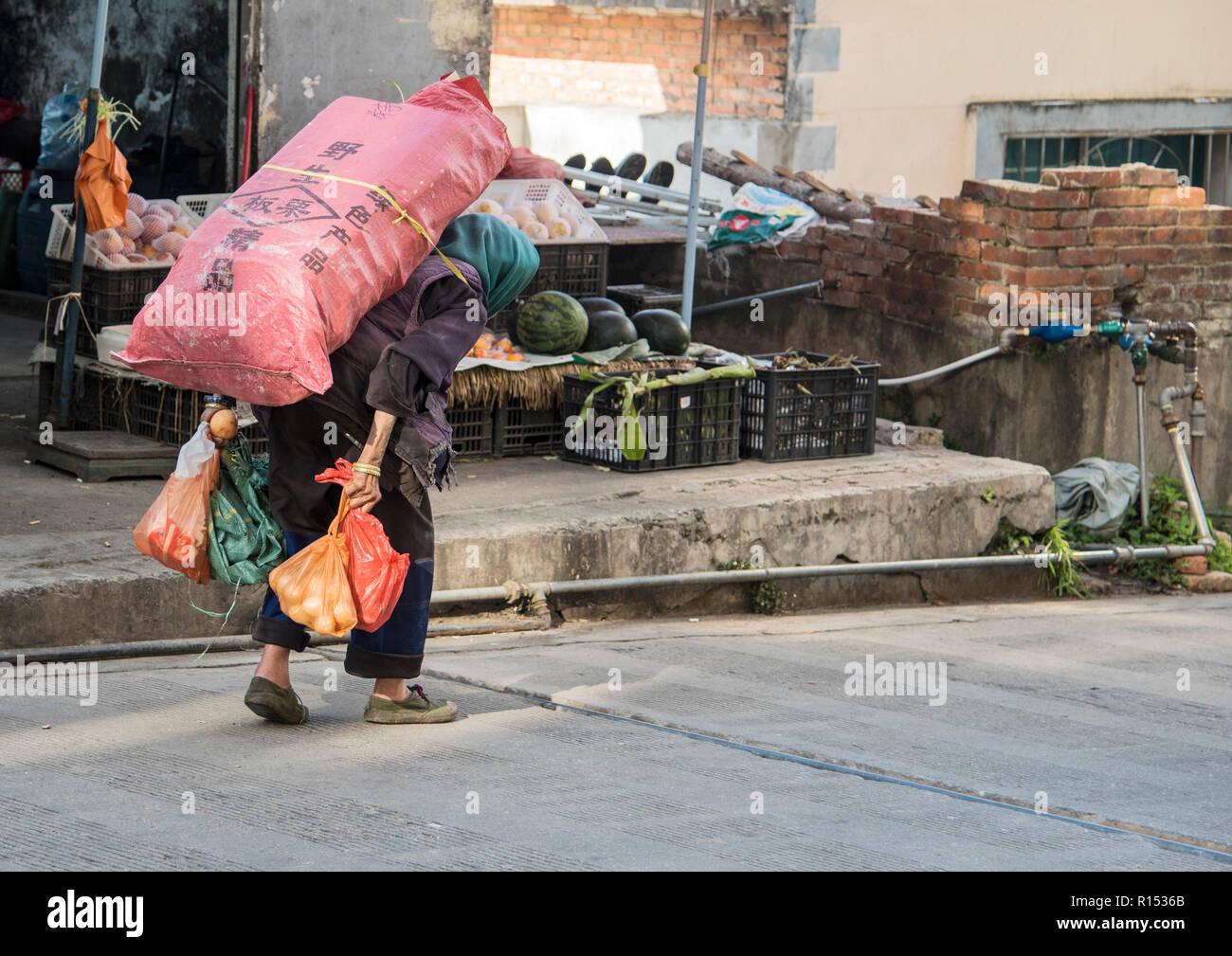 Une vieille femme chinoise transportant une lourde charge et de trouver qu'il est très fatiguant de marcher la Chine Photo Stock