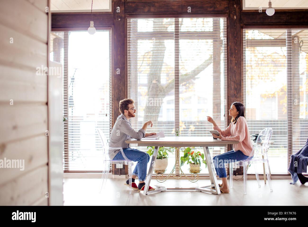 Un homme et une femme sont assis à une table en face de l'autre. Banque D'Images