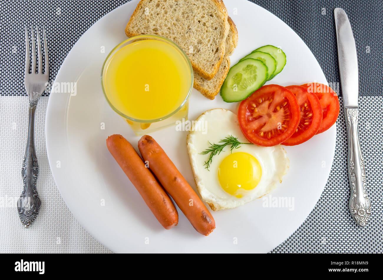 Le petit-déjeuner sur une table dans un œuf frit saucisses frites en forme de cœur, des tranches de légumes concombres et tomates, jus, pain de mie, couteau et fourchette, Banque D'Images