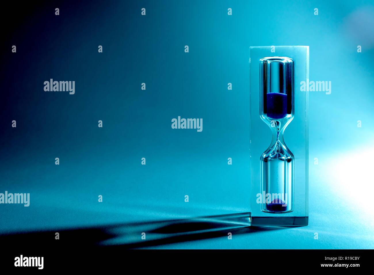 Sablier Hourglass avec ombres et l'éblouissement du soleil sur un fond bleu. Old style retro vintage photo. La texture du sable, la chute du sable. Banque D'Images