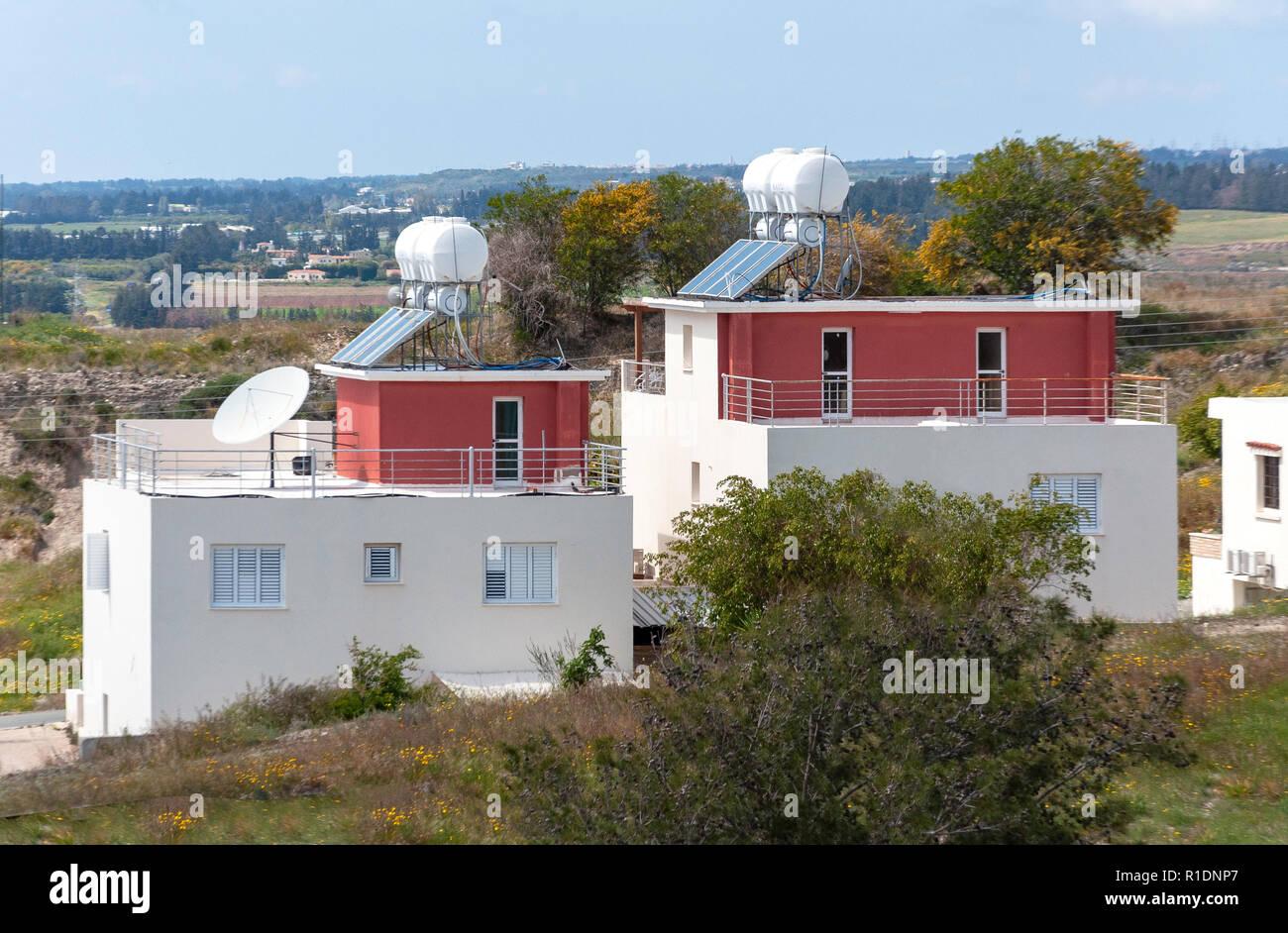 Nouvelles maisons avec des panneaux solaires et des réservoirs d'eau, Kouklia, Pafos District, République de Chypre Photo Stock